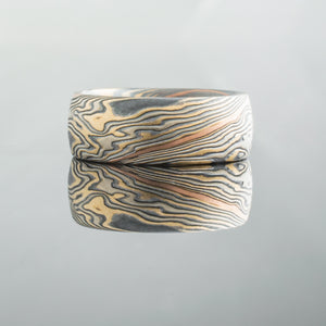 Mokume Gane Ring or Wedding Band in Flare Palette and Twist Pattern with added Red Gold Stratum