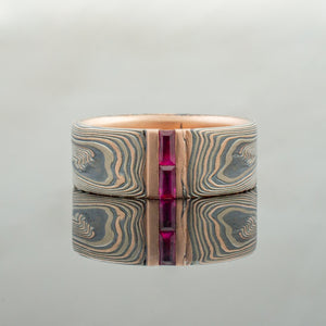 Mokume Gane Wedding Ring or Band in Vortex Pattern and Embers Palette with emerald cut rectangular Rubies and Sapphires red stones blue stones stripe channel set woodgrain Pattern black blackened oxidized silver palladium alternative metal nature inspired rustic artisan topographical earthy style unique handmade matching wedding bands mens womens