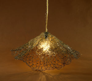Woven brass wire looped light shade funnel shaped with a single bulb from a wire adorned white cord