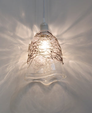 Clear blown glass pendant light bell shape accented by woven blackened copper wire scribble lines on the top half of the bell shape. Hangs from a white cord