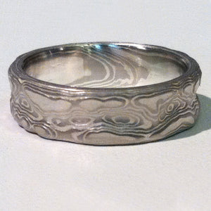 "This Mokume Gane ring is patterned in the ""Guri Bori"" style which leaves the carved surface as relief showing the layers like topographic lines which match the contours of the carving.  Reminiscent of swirling water, clouds, wind blown snow or canyons this ring has a unique tactile beauty.  Shown here in a 6mm wide band with the palladium and silver metal combination and an etched finish."