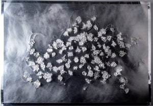 Silver embossed drawing on aluminum with small glass clusters floating off surface on wires