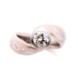 Mokume gane ring or wedding ring bypass style arn krebs, woodgrain pattern embers palette, red gold palladium and silver, white diamond in collet