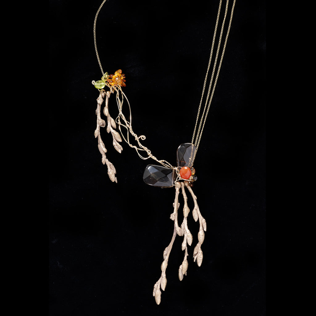A stunning piece featuring cast bronze budding twigs with carnelian, peridot, and citrine with cascading gold filled chain.