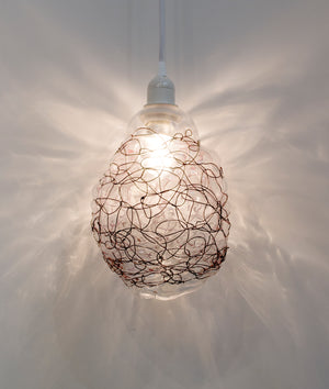 Clear blown glass pendant light accented by woven blackened copper wire scribble lines all over.