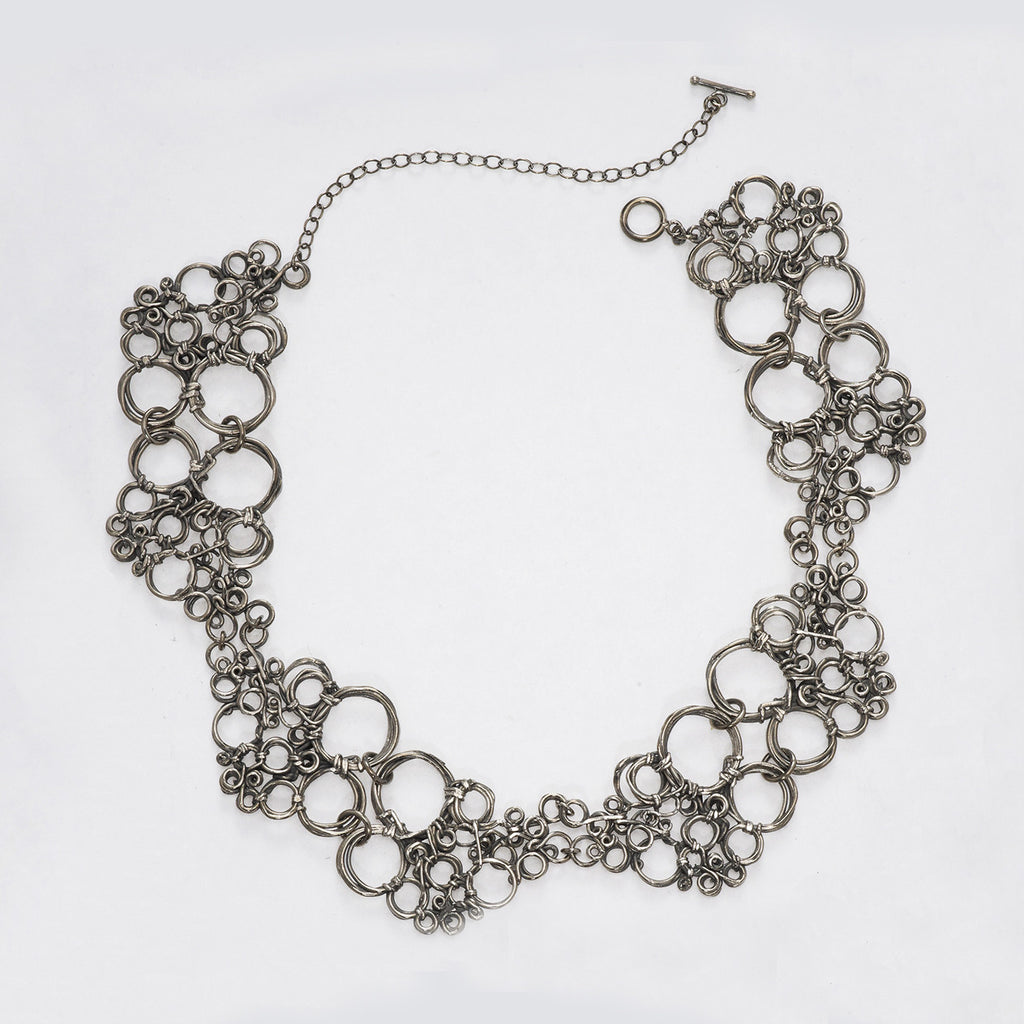 "This stunning piece features an organically designed repeating element to create movement and flow. Each piece moves freely to lay comfortably on the neck.   Oxidized silver. 18"" length."