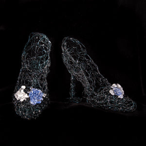 Black wire sculpture of a pair of womens heels with blue and clear glass clusters on the toes