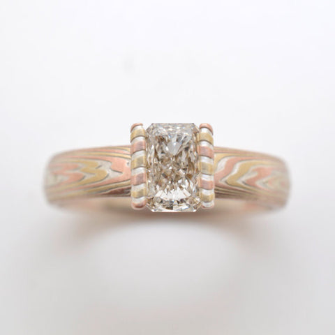Mokume Gane Engagement Ring in 14kt Yellow gold, 14kt Red Gold and sterling silver with a floating channel set radiant cut diamond