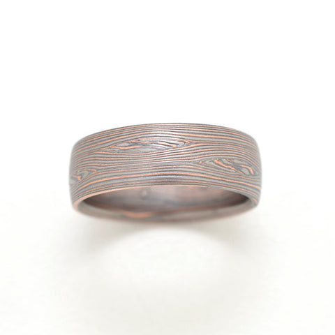 Mokume Ring In Palladium, 14kt Red Gold, and Oxidized Silver in flow pattern with mokume knots with an etched and oxidized finish