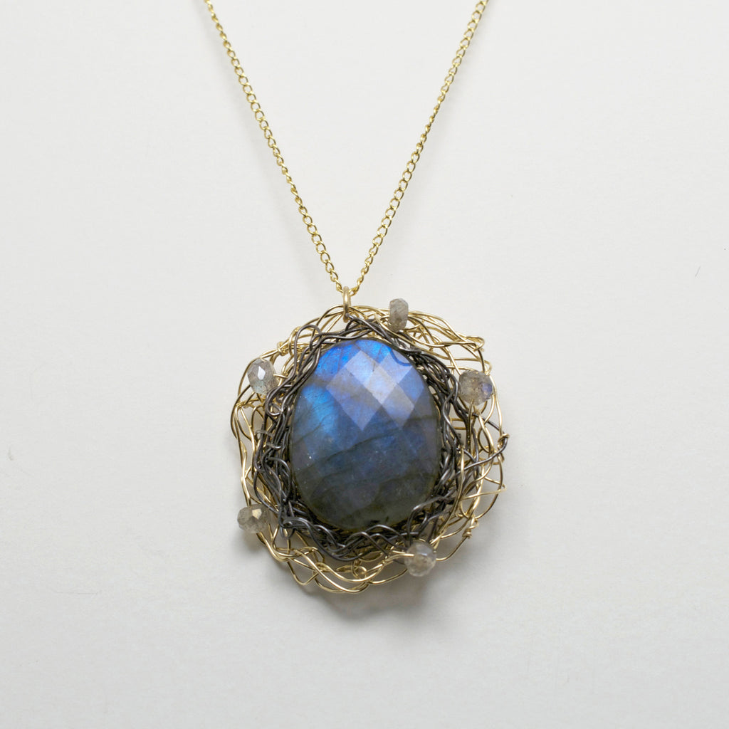 "This spun pendant is made from hand woven layers of 14 kt gold filled wire and oxidized silver.  The centerpiece is a labradorite stone surrounded by smaller labradorite beads. Paired with a 1mm gold filled chain.  1"" Diameter pendant"