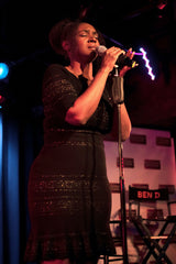 Saycon singsin club wih microphone in black dress with gold accents