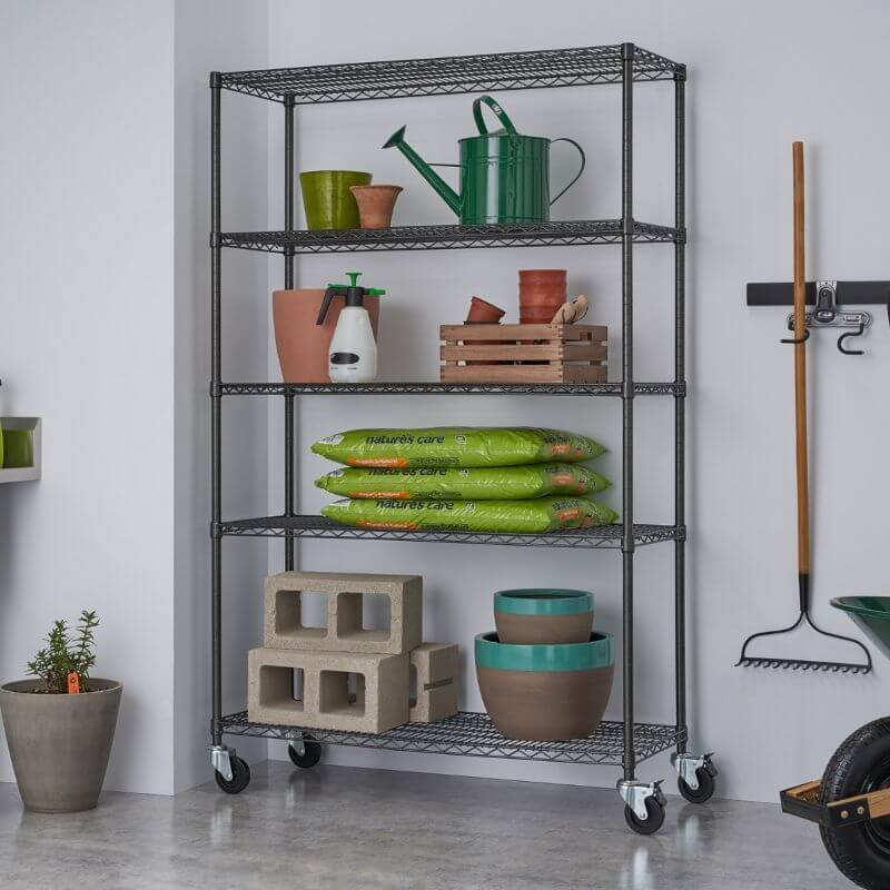 Trinity TBFPBA-0924 (48x18x72) PRO 5-Tier Wire Shelving w/ Wheels in Black Anthracite Color. Shown with common gardening tools. View from the front right.