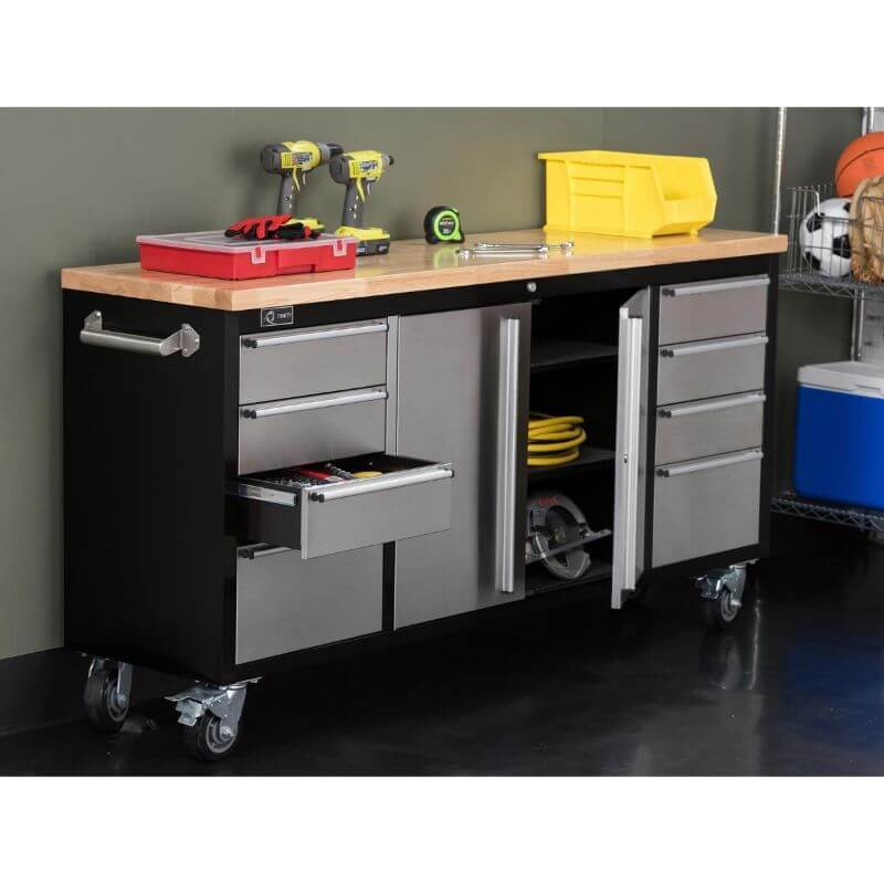 Trinity TLS-7205 (72x19) Black & Stainless Steel Rolling Workbench with some of the drawers opened. Placed against a wall with tools displayed on the worktop.