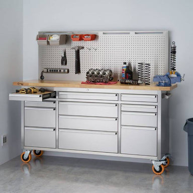 Trinity TLSF-7210 (72x19) PRO Stainless Steel Rolling Workbench w/ Pegboard. Has building/Construction Tools on the Worktop and Pegboard. Top left drawer with Wood Worktop is Opened. Placed next to a wall.