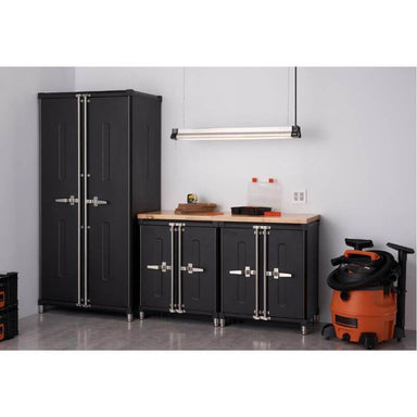 Trinity TSNPBK-0615 (4-Piece) PRO Garage Cabinet Set in Black Placed Against a Wall in a Garage with Drawers Closed.