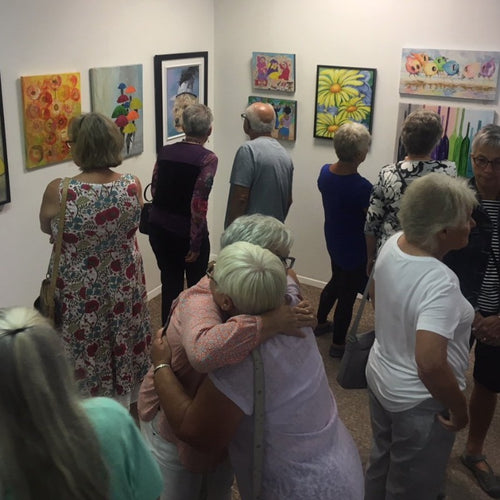 Crowd of people looking at paintings at a gallery opening