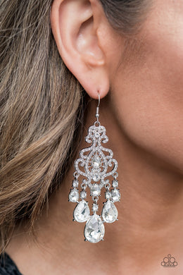 Gradually increasing in size, glassy white teardrop gems create a dramatic fringe at the bottom of a decorative silver frame swirling with dainty white rhinestones for a timelessly over-the-top sparkle. Earring attaches to a standard fishhook fitting.  Sold as one pair of earrings.