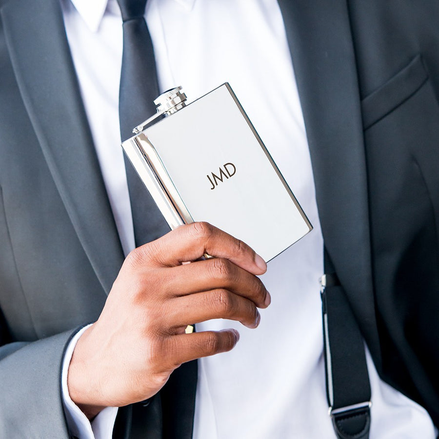 a guy in a suit holding a flask monogrammed with JMD