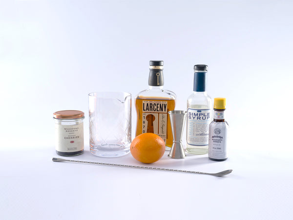 Ingredients for an old fashioned: From left to right - Jar of bourbon glazed cherries, mixing glass, Larceny Bourbon, Simple syrup, bitters, large metal spoon and an orange.
