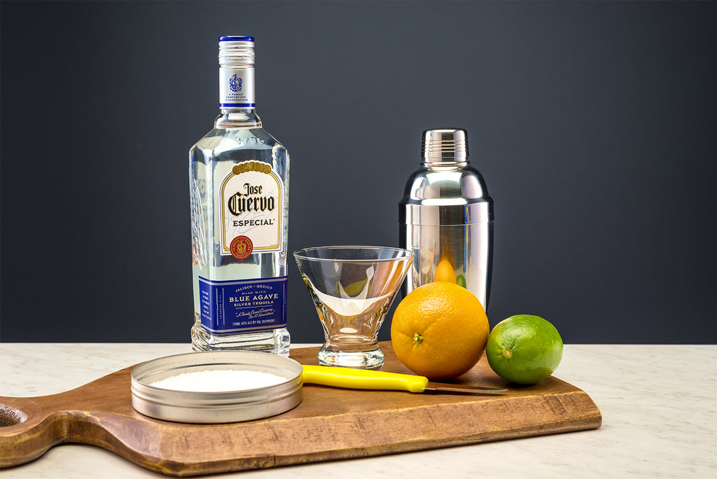 Ingredients for a skinny margarita on a wooden cutting board. From Left to right: Coarse salt, José Cuervo Tequila, margarita glass, paring knife, orange and lime.