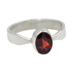 A very delicate ring in sterling silver with a small faceted oval Garnet stone.