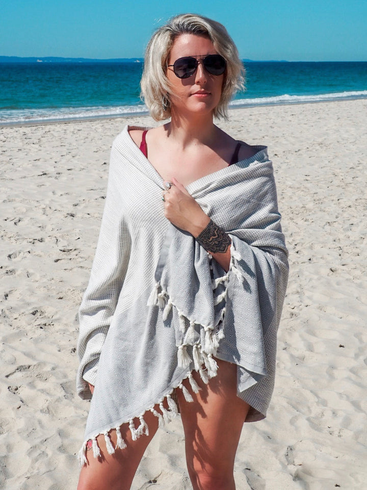 Beautiful women standing on an Australian Beach, Wrapped in a Collie and Co Turkish Towel, lightweight towel, super absorbent towel, fast drying towel, portable towel, Travel and adventure towel, Turkish Beach Towel. The Colour is Smoke Grey. It is a patterned towel.