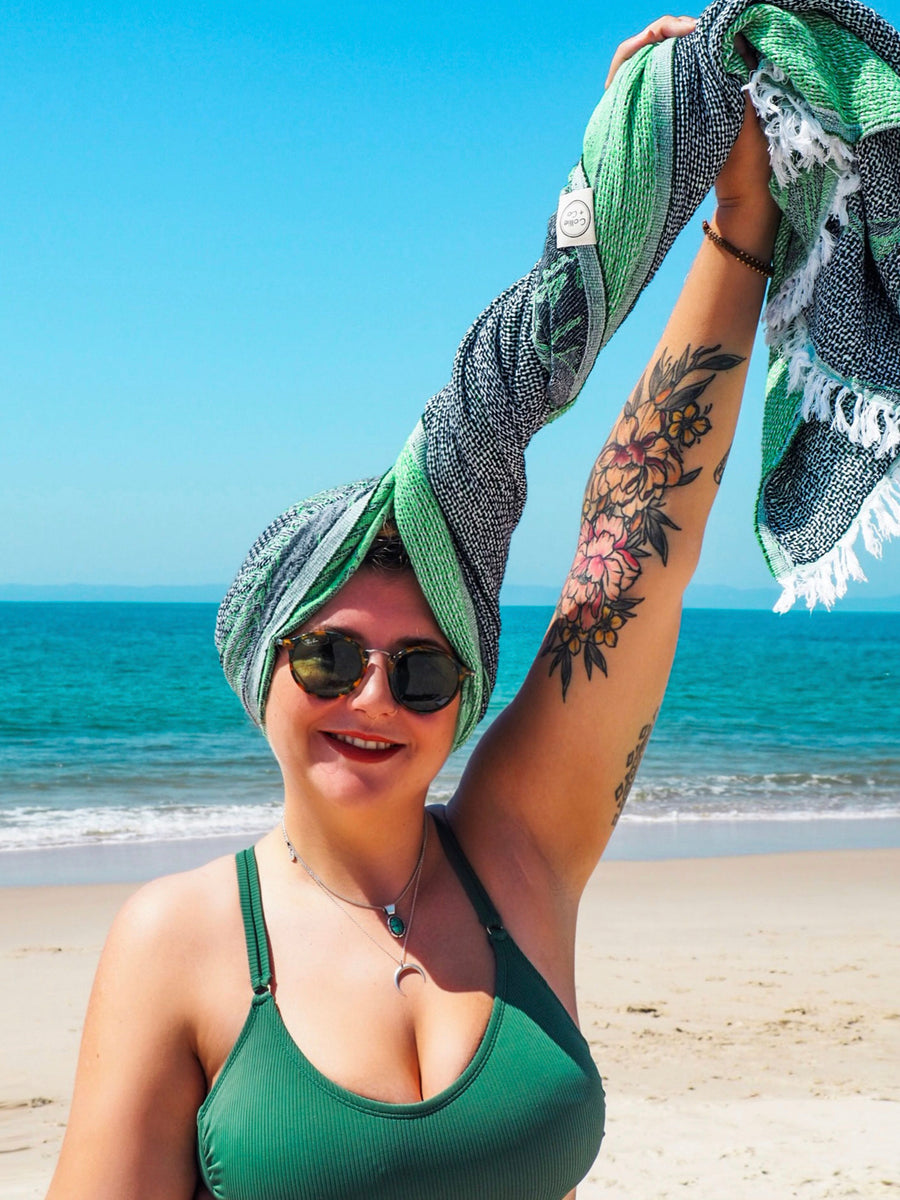 Beautiful women standing on an Australian Beach, Wrapped in a Collie and Co Turkish Towel, lightweight towel, super absorbent towel, fast drying towel, portable towel, Travel and adventure towel, Turkish Beach Towel. The Colour is emerald green with a palm tree print in the pattern. It is a patterned towel.