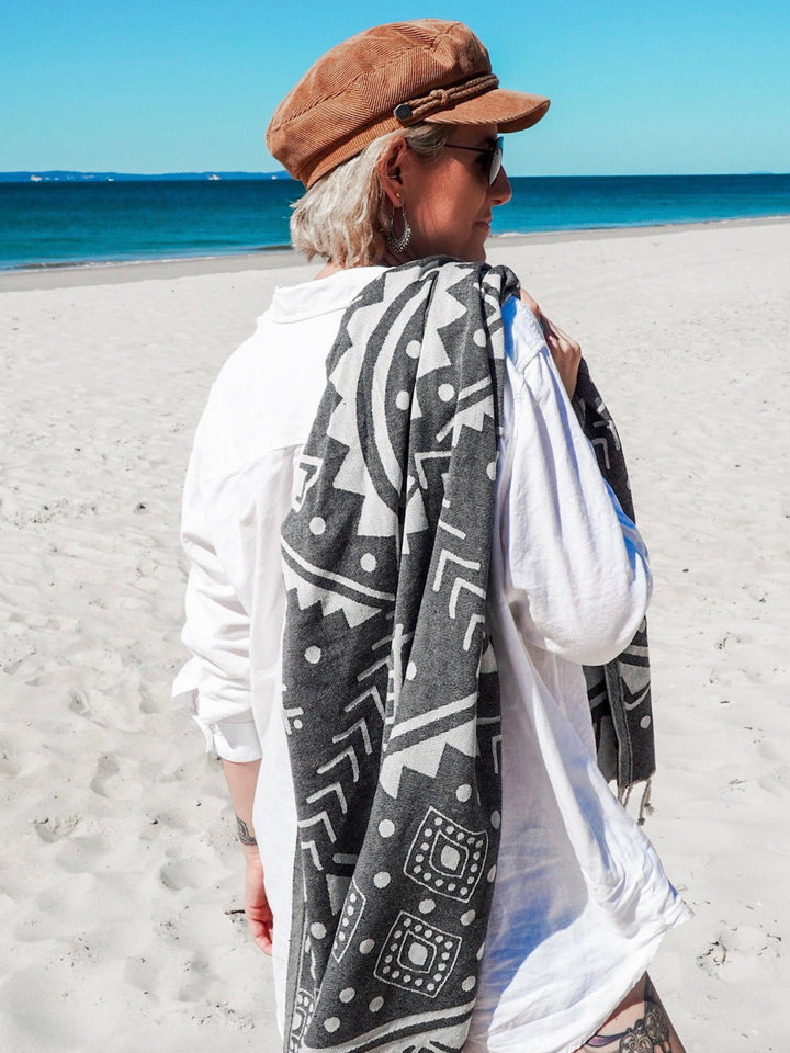 Beautiful women standing on an Australian Beach, Wrapped in a Collie and Co Turkish Towel, lightweight towel, super absorbent towel, fast drying towel, portable towel, Travel and adventure towel, Turkish Beach Towel. The Colour is Shadow grey with a Native American Indian Navajo inspired pattern. It is a patterned towel.