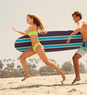 Couple running on the beach with surfboard. Flexpower Bath Salts