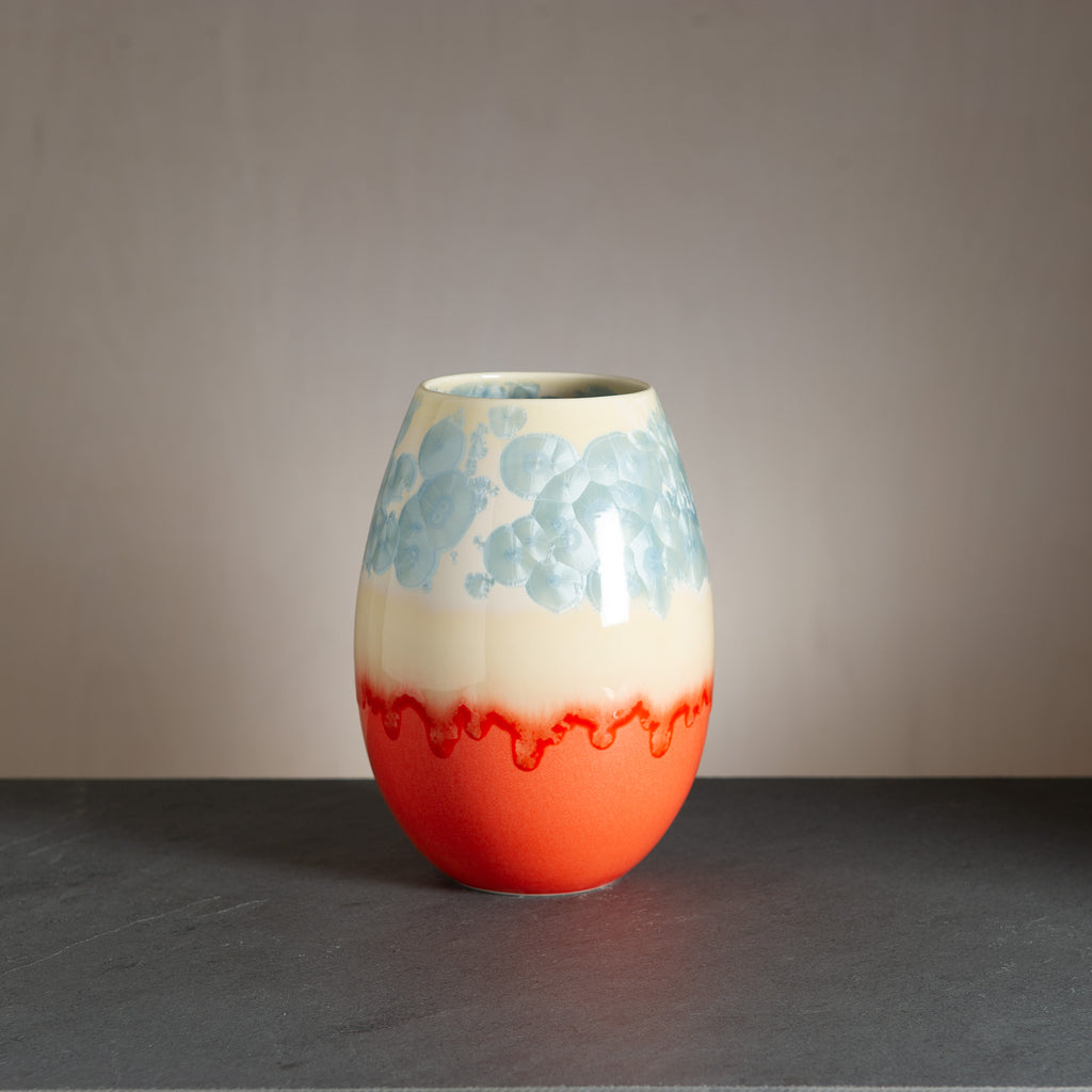 Unique, handmade crystal vases from WAUW design in Østerbro. This variant has a brilliant orange bottom and cream-colored top with light blue crystals.