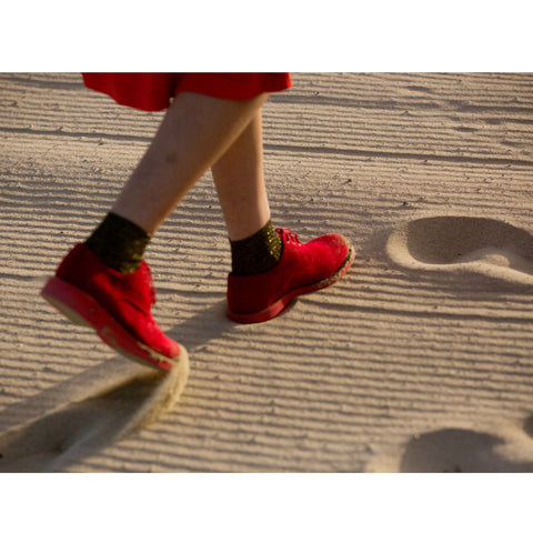 woman with red shoes walking in the sand