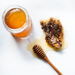 Honeycomb and honey dipper covered in honey, next to a glass honey jar on a light marble surface.