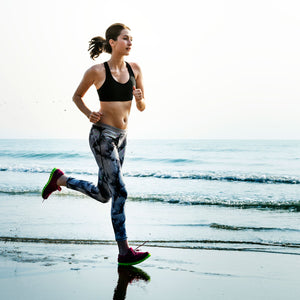 Woman in athletic clothing running on a sandy beach next to the water.