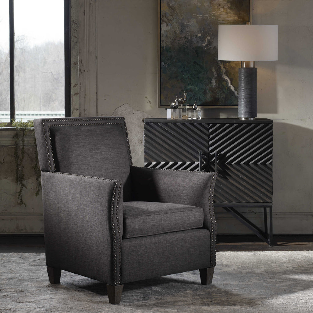 Charcoal grey linen club chair with antique brass nailhead trim with solid walnut legs