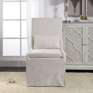 White linen blend slipcover-look armless chair with a plush cushion seat and kidney pillow