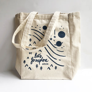 Let's Go Explore canvas tote front with land and space designs