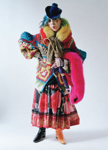 ANNA PIAGI DRESSED IN PATCHWORK AND ODD BOOTS WITH WALKING STICK AND FAUX FUR