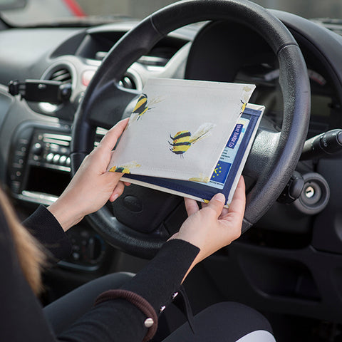 Hands opening a Blue Badge Wallet in Busy Bees design inside a car, in front of the steering weel