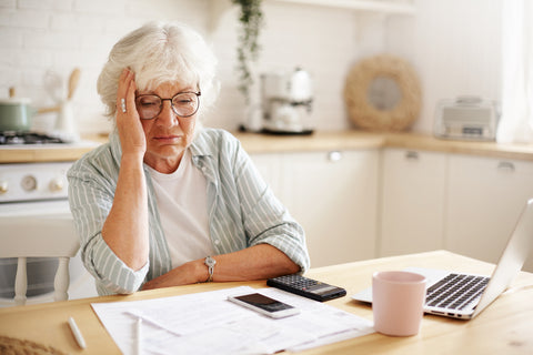 Distressed older woman with calculator and laptop trying to organise budget