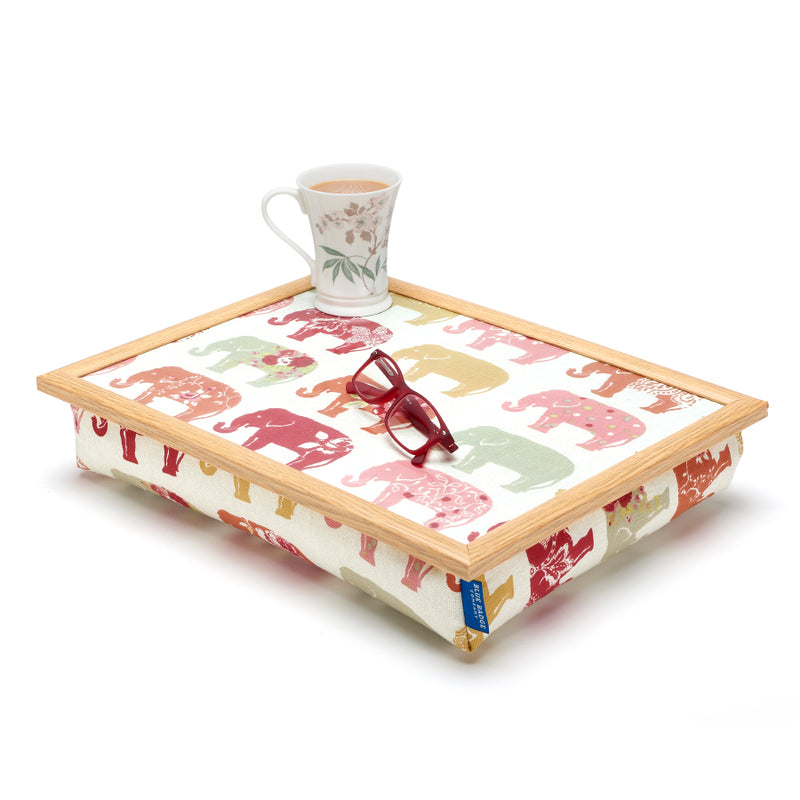 Bean Bag Lap Tray in Nelly Elephant print against white back ground with a full mug and a pair of glasses on top
