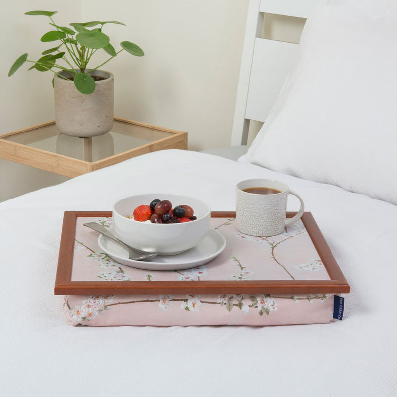 The Cherry Blossoms lap tray on a white bed in a minimalist room with a plant in the background. There's a bowl of fruit and a full mug on the tray.
