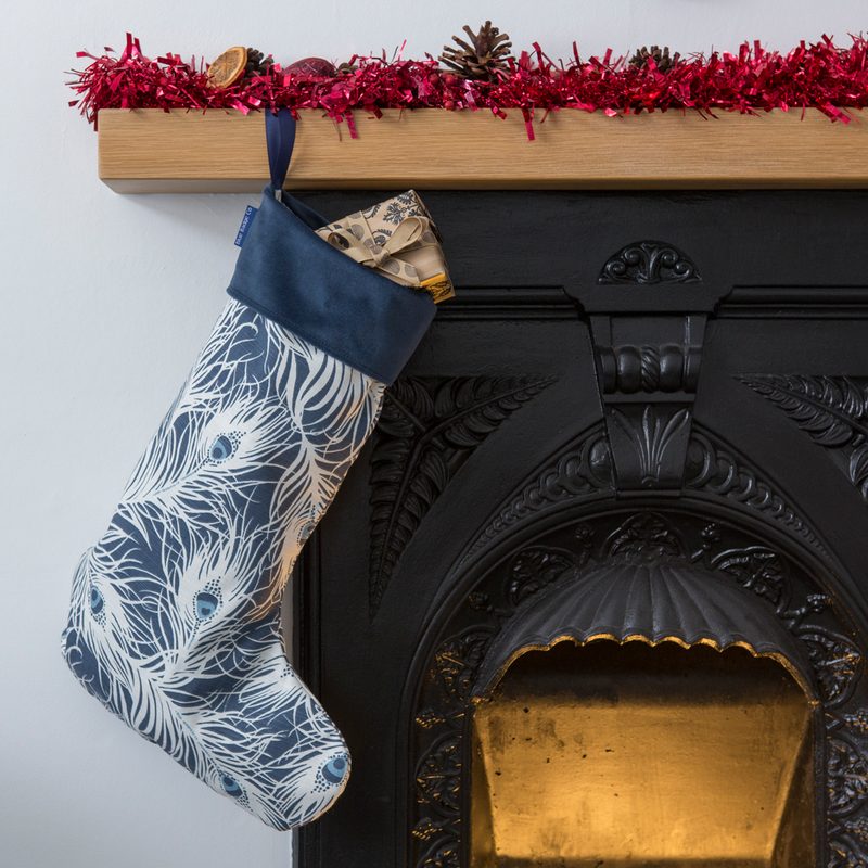 Christmas Stocking in Peacock Design with Navy Velvet Top hanging from a fireplace with presents inside