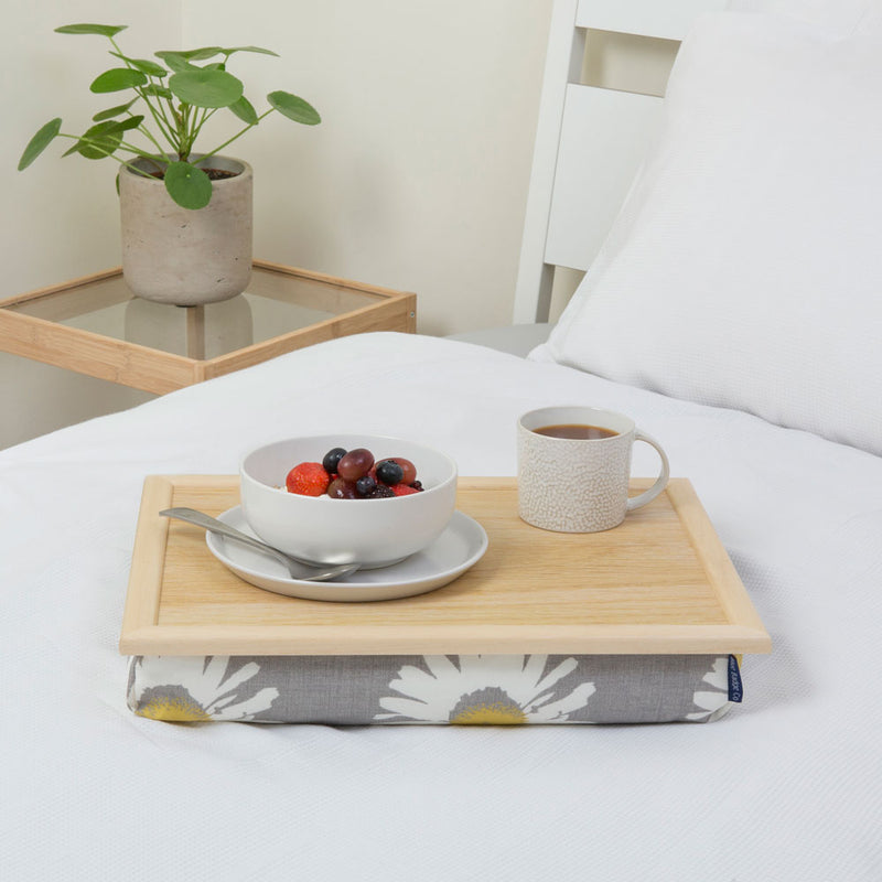 Bean bag lap tray in Grey Daisy on a white bed with a bowl of fruit and a full mug on top.