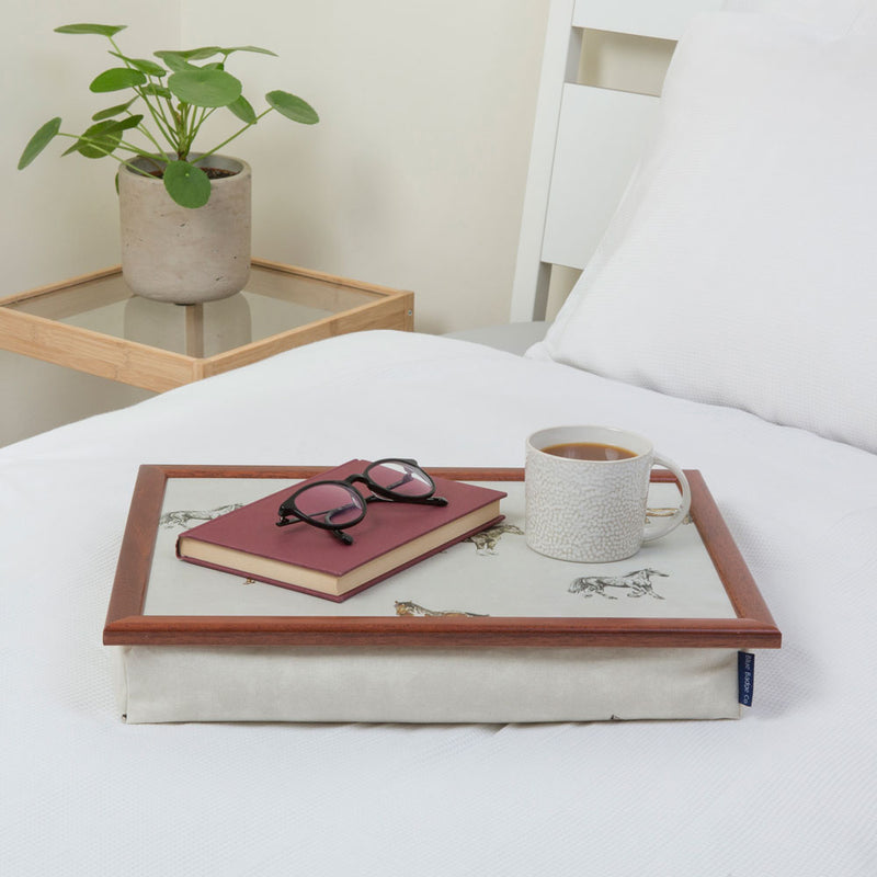 Bean bag lap tray in Horse and Pony print on a white bed with a book, a pair of glasses and a full mug on top