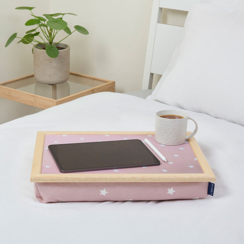 Bean bag lap tray in Pink Star print on a white bed with a tablet and a full mug on top