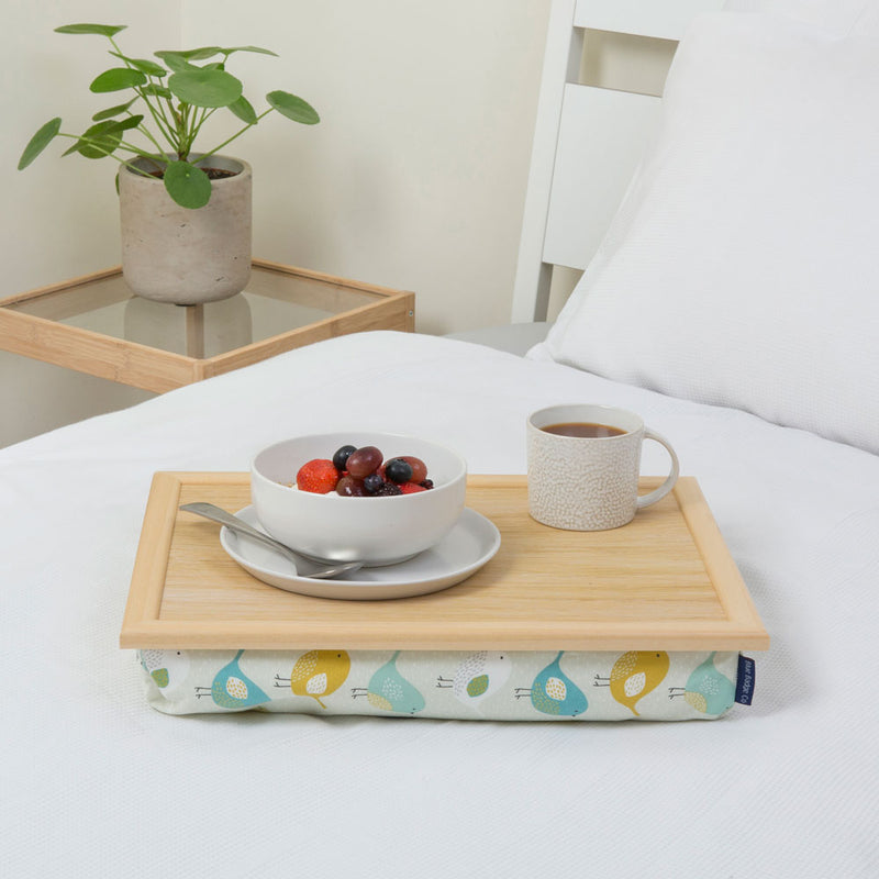 Garden Birds bean bag tray on a white bed with a bowl of fruit and a full mug on top.