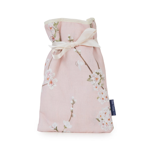 Mini Hot Water Bottle with in Cherry Blossoms with white satin ribbon and blue badge company label showing