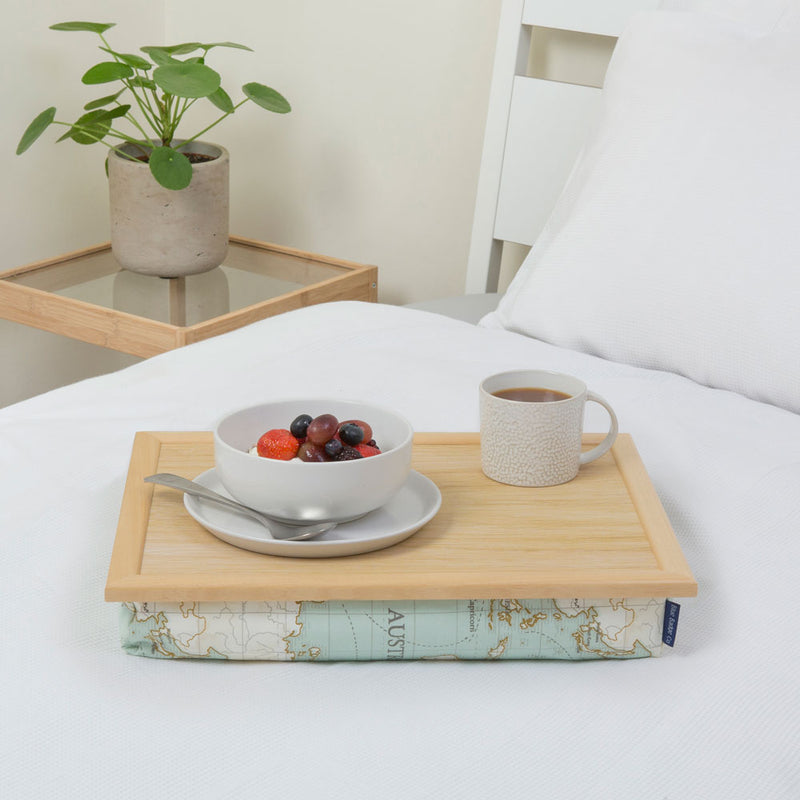 Bean bag lap tray in World Map print on a white bed with a bowl of fruit and a full mug on top.