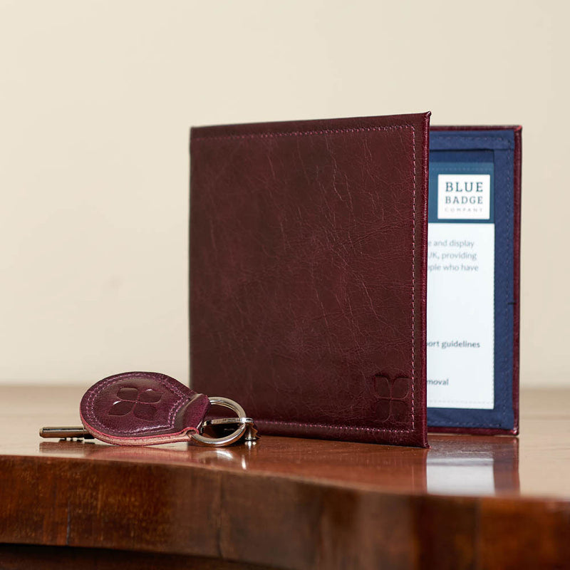 Leather Blue Badge Wallet, Keyring and RADAR Disabled Toilet Key in Burgundy with blue badge company logo embossed on both items and placed on wooden table at home