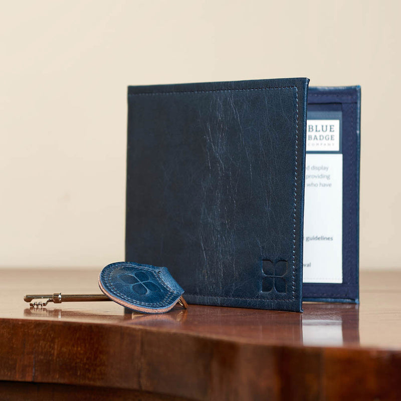 Leather Blue Badge Wallet, Keyring and RADAR Disabled Toilet Key in Navy with blue badge company logo embossed on both items placed on kitchen table
